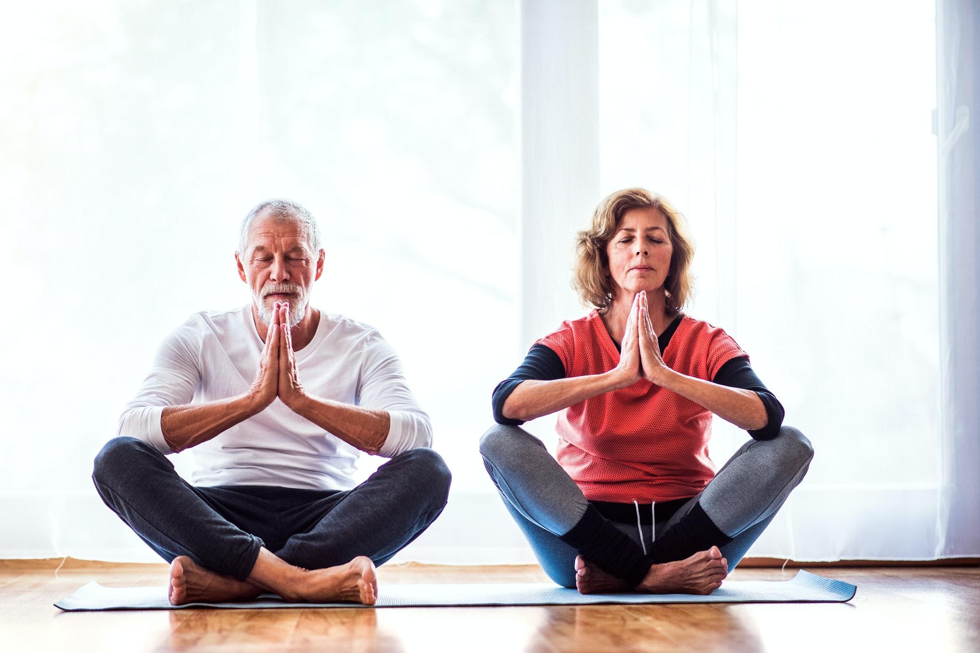 Senior couple meditating at home.